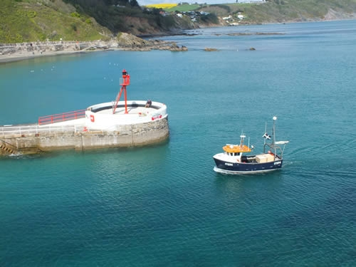 A fishing boat rounds the Banjo Pier at Looe
